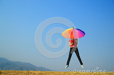 Multicolor umbrella woman jumping to sky