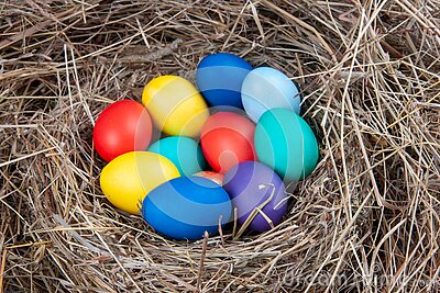 Multicolored eggs in a nest in the hay. Concept easter Stock Photo