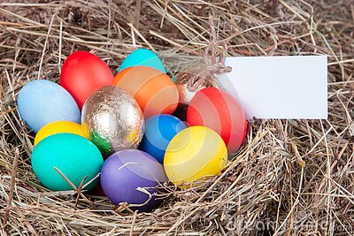 Multicolored eggs with a note in the hay. Mock up, concept easter Stock Photo