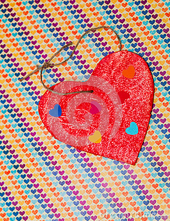 Multicolored paper hearth on a wooden red heart