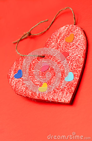 Multicolored paper hearths on a wooden red heart