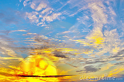 Multicolored sunrise with golden football ball