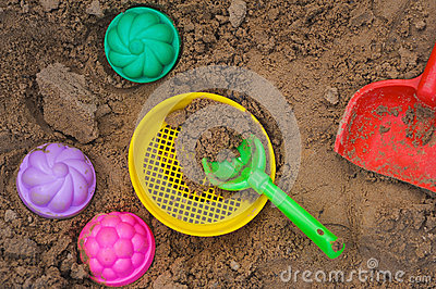 Multicoloured toy lying on a wet sand