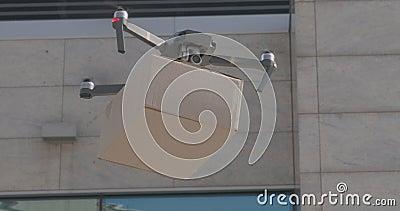 Multicopter entrega paquete de cartón en el área de la ciudad almacen de video