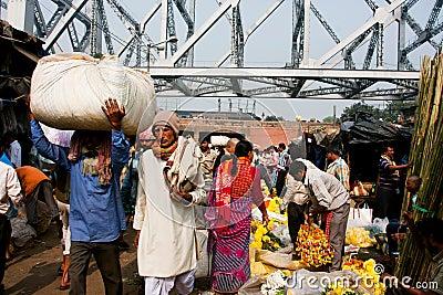 A multidão de povos asiáticos apressa-se com as fileiras do mercado da flor em Calcutá Fotografia Editorial