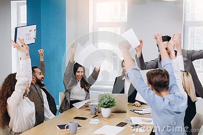 Multiethnic diverse happy team celebrate project success throw paper up together. Corporate community, college graduation, startup Stock Photo