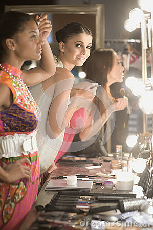 Multiethnic Models Applying Makeup In Dressing Room Mirror Stock Photo