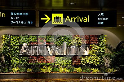 Multilingual arrival sign and flowers at airport Editorial Photo