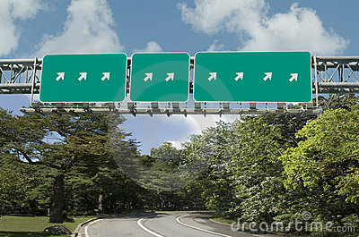 Multiple highway signs pointing in same direction