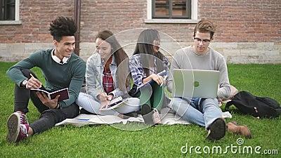 Multiracial группа в составе друзья изучая совместно на кампусе видеоматериал