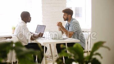Multiracial partners handshaking making good deal in cozy loft office. Multiracial partners making good business deal in cozy loft office, african and caucasian stock video