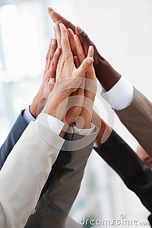Multiraciale handen die samen in overeenkomst worden opgeheven