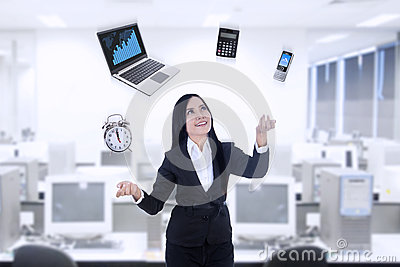 Multitasker businesswoman using laptop, calculator, phone, clock