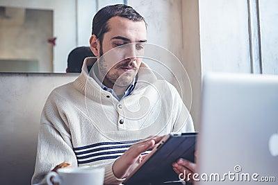 Multitasking man using tablet, laptop and cellhpone