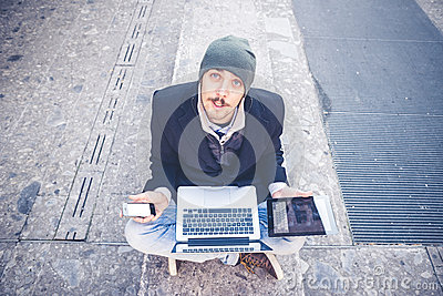 Multitasking man using tablet, laptop and cellhpone