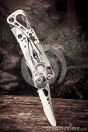 Multitool, multi purpose tool with knife stuck on Stock Photo