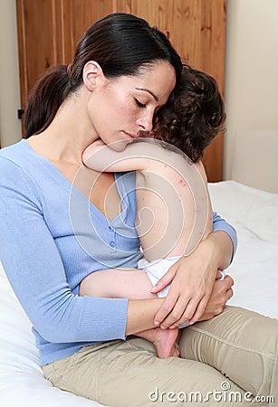 Mum comforting sick baby