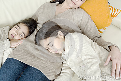 Mum and daughters sleeping on couch