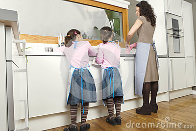 Mum and Daughters Washing Up In Kitchen