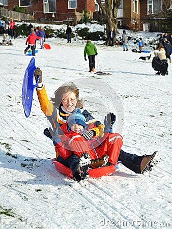 Mum e filho no sledge que desliza o monte nevado, inverno
