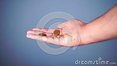 Muntstukkendaling van een hand op een blauwe achtergrond stock footage