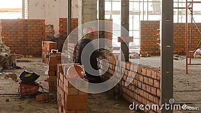 Muratori che pongono i mattoni per fare un timelapse delle pareti stock footage