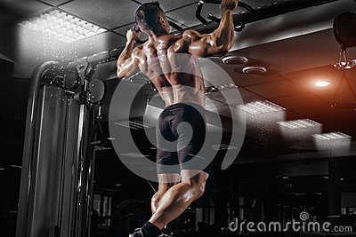Muscle athlete man in gym making pull up Stock Photo