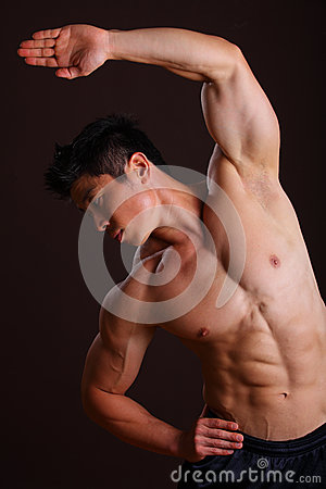 Muscle man stretching left arm and abs