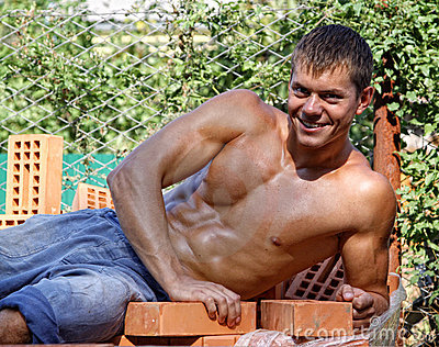 Muscle sexy young worker lying on bricks