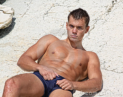 Muscle wet sexy naked man lying on rock