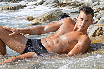Muscle wet sexy naked man lying in sea water