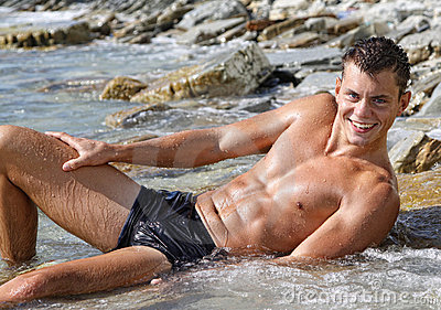 Muscle wet smile sexy naked man lying in sea water