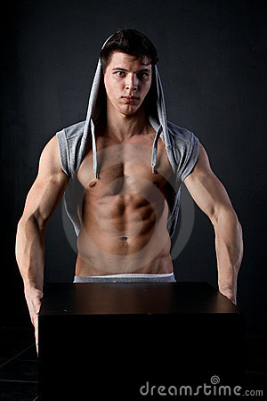 Muscle young boy hold black cube in the dark
