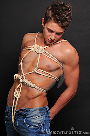 Muscled man bound with rope