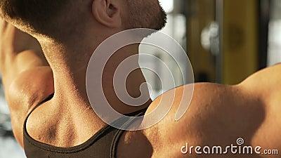 Muscleman που επιλύει με να κάνει pull-down την άσκηση στη γυμναστική, ισχυρό αρσενικό σώμα φιλμ μικρού μήκους