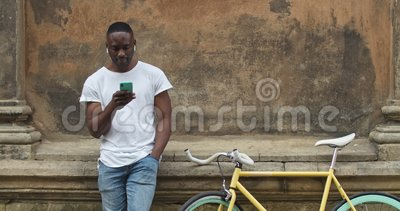 Muscular Africano Jovem em Sfones Usando seu Smartphone, Olhando para a Tela e ao Lado enquanto Permanece video estoque