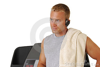 Muscular athletic man leaning on a treadmill