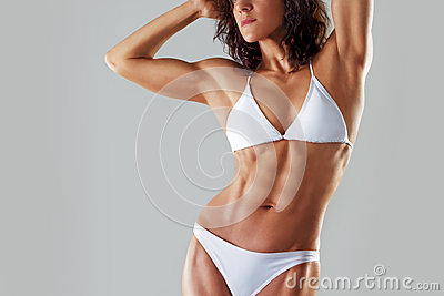Muscular athletic young woman in a white bathing suit . Fitness