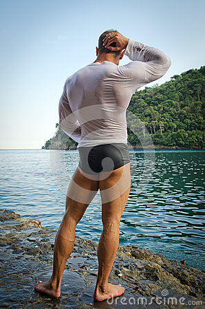 Muscular bodybuilder facing the sea, seen from the