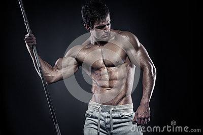 Muscular bodybuilder guy doing posing with dumbbells