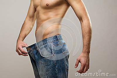 Muscular fit man wearing big jeans after diet