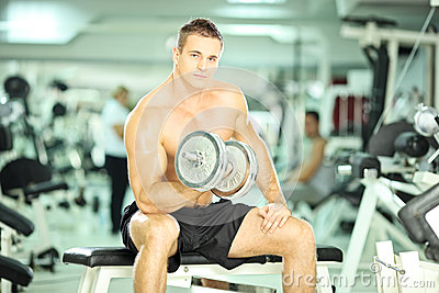 Muscular guy lifting weights in a gym