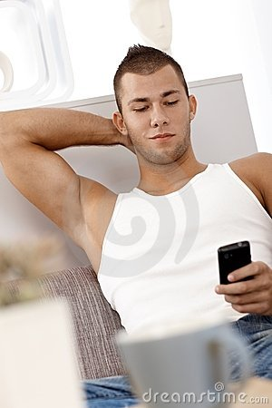 Muscular guy texting on sofa