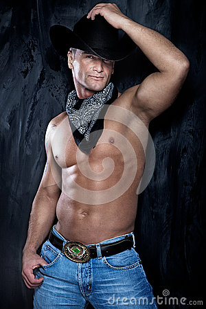 Muscular handsome man posing in a cowboy hat and jeans over the
