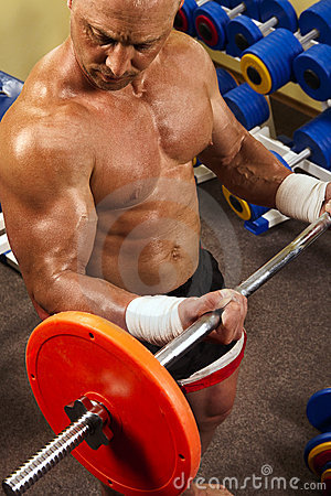 Muscular man with a bar weights in hands training