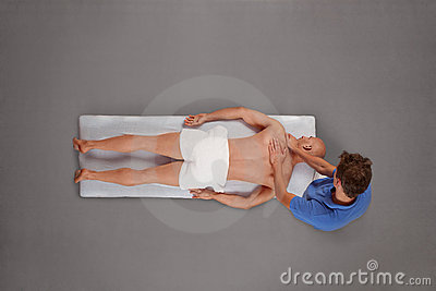 Muscular man being massaged by therapist