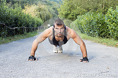 Muscular man doing pushup in the park.