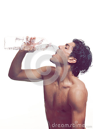 Muscular man drinks water