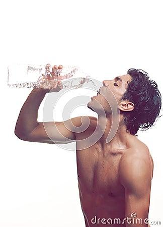 Muscular man drinks water