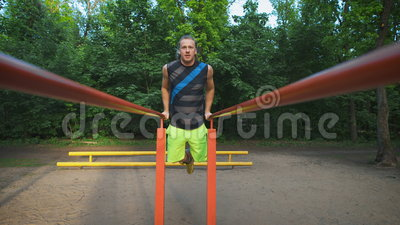 Muscular man during his workout in park. Dips, exercise chest and triceps. Video shot in 4K stock footage
